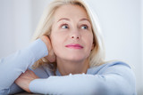 Active beautiful middle-aged woman smiling friendly and looking in camera. Woman's face closeup. Realistic images without retouching with their own imperfections. Selective focus. - 230220455