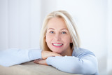 Active beautiful middle-aged woman smiling friendly and looking in camera. Woman's face closeup. Realistic images without retouching with their own imperfections. Selective focus. - 230220470