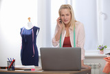 Discussion of the project of clothing design with the client by phone, Skype. Beautiful European woman talking on phone while standing near the table in the workshop with clothes hanging in background - 230220645