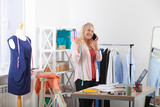 Search for new ideas for business. Beautiful European woman working in the office, standing near the table in the workshop with clothes hanging in the background. Interier design studio. - 230220656