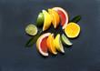 Leinwanddruck Bild - Tropical fruits, Südfrüchte, Zitrusfrüchte, in Scheiben, auf schwarzem Schiefer, von oben, Textraum, copy space