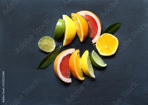 Leinwanddruck Bild Tropical fruits, Südfrüchte, Zitrusfrüchte, in Scheiben, auf schwarzem Schiefer, von oben, Textraum, copy space