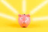 Leuchtendes Sparschwein vor gelbem Hintergrund - 230232295