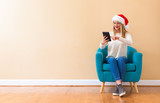 Yong woman with santa hat using her tablet in a chair