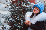 christmas portrait of happy woman with burning firelight walking outdoor in snowy winter city in fashion coat with white fur and oversize chunk knit hat - 230243894