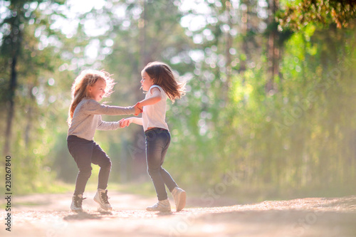 Two little girls dancing and having fun together outdoors - 230267840