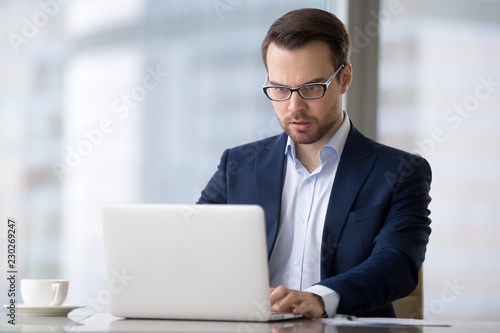 Leinwanddruck Bild Tensioned or surprised caucasian man is sitting in office and typing on laptop. Serious and concentrated male in suit is working at notebook and looking resent and worried