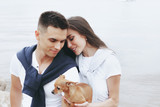 Young beautiful positive couple with small dog sitting on stone by sea