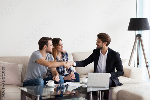 Leinwanddruck Bild Young couple, family at meeting with realtor, interior designer, decorator, landlord making deal. Husband handshaking with man in suit. Concept of meeting with client, customer