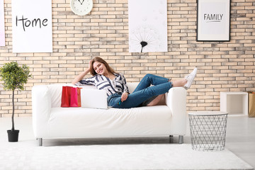 Young woman shopping online with credit card and laptop on sofa