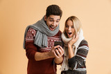 Excited young loving couple in sweaters using mobile phone listening music isolated over beige background.