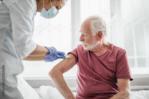 Leinwanddruck Bild Best treatment for you. Portrait of bearded old man receiving vaccine shot in hand while sitting on hospital bed