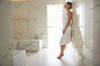 Peaceful lady wearing white towel and standing on her toes next to the wall of hammam