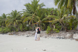 Group of friends chatting on a beautifu tropical sandy beach. Rest on an exotic tropical island, on a deserted beach - 230298820