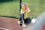 Happy lady smiling while sitting at the sports ground alone - 230300631