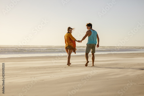 Foto Murales Couple walking on beach holding hands