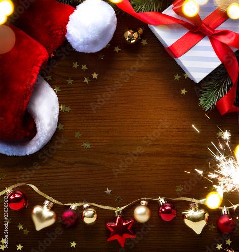 art Santa hat and Christmas tree decoration on wooden background © Konstiantyn