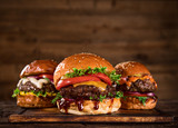 Tasty burgers on wooden table. - 230307459