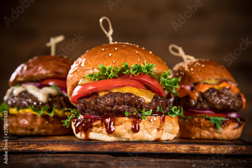 Tasty burgers on wooden table. - 230307432