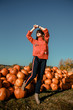Young woman on a pumpkin farm. Beautiful girl near pumpkins. A girl with a pumpkin