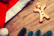 Gingerbread man and christmas hat on wooden table.