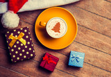 Cappuccino with christmas hat and gift on wooden table. - 230317861