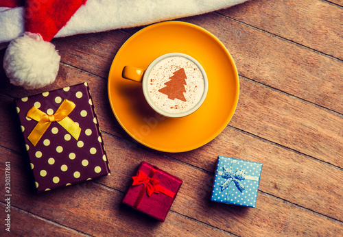 Leinwandbild Motiv Cappuccino with christmas hat and gift on wooden table.