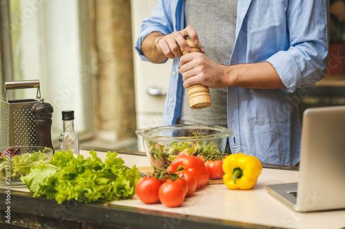 Close-up of young man preparing delicious and healthy food in the home kitchen on a sunny day.