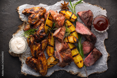 Assorted grilled meat and potatoes on black background - 230360002