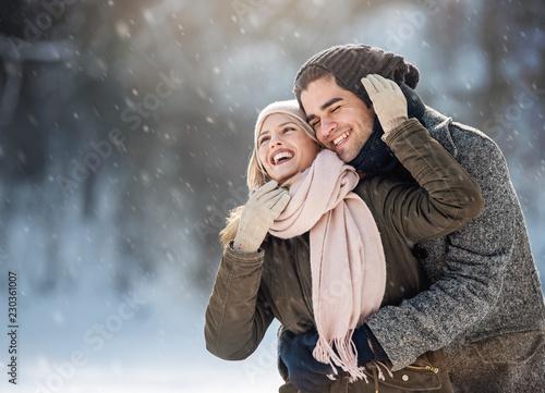 Leinwanddruck Bild Two young people enjoying in the snow