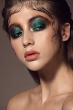 Close up portrait of beautiful woman face with bright green make up. - 230363447