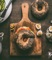 Bagel bread on cutting board topped with salmon, avocado, cooked quail eggs and fresh cheese on dark rustic wooden background, top view.