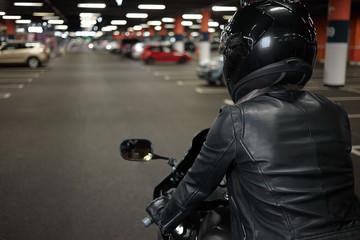 Rear view of unrecognizable woman wearing stylish motorcycle leather jacket, gloves and safety helmet, sitting in her two wheeled motor vehicle in underground garage or car parking, ready to drive