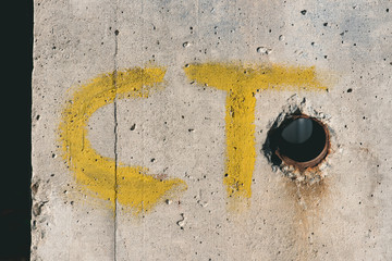 yellow ct letters on white concrete wall