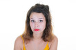 young curly woman pouting and grimacing with her red lips
