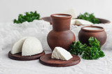 homemade cheese, cottage cheese, milk and greens on white background in pottery. - 230387077