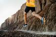 man athlete running on mountain trail in sunlight