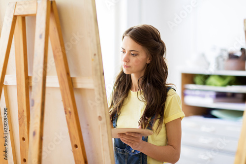 Leinwanddruck Bild art school, creativity and people concept - student girl or young woman artist with easel and palette painting at studio