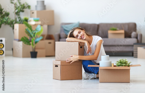 Leinwanddruck Bild happy   girl with boxes moves to new apartment