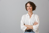 Happy young business woman posing isolated over grey wall background. - 230407433