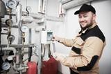 heating engineer or plumber inspector in boiler room taking readouts or adjusting meter - 230408823