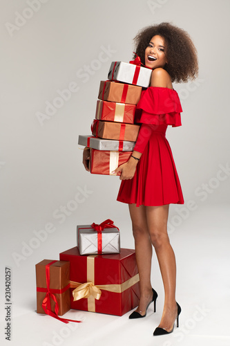 Leinwandbild Motiv Female model wear red dress keeps gifts
