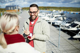 Excited bearded Caucasian man proposing to his girlfriend outdoors, holding engagement ring, showing fuck after refusal and smiling cheerfully - 230421858