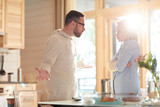 Young married Caucasian couple arguing about household duties while standing in home kitchen illuminated with bright morning sun - 230421890