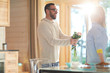Cheerful bearded Caucasian man presenting small pretty bouquet of flowers to his girlfriend while standing in bright sunlit kitchen