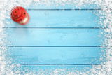 Christmas background. Blue frozen wooden table with snowy snowflakes on edges. Red lantern on left side. Copy space in the middle. - 230428872
