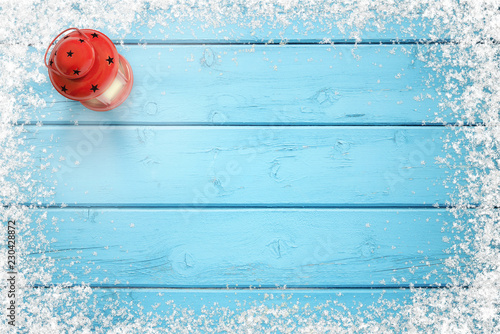 Christmas background. Blue frozen wooden table with snowy snowflakes on edges. Red lantern on left side. Copy space in the middle.