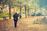 senior walking at the park in fall season, back view of lonely man on a walk in autumn town  - 230429011