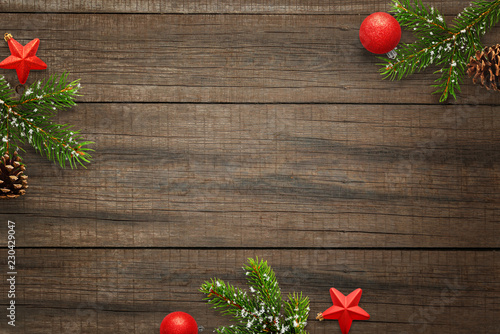 Wooden table with Christmas decorations and space in the middle for text. Christmas composition with star and ball decorations, fir branches and cones.