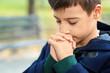 Leinwanddruck Bild - Little boy praying outdoors